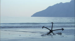 A boat anchor situated at the shore of a beach. Stock Footage