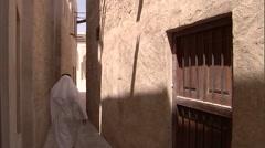 An Arabic man walks down a narrow passage in the Bastakiya area in Dubai. Stock Footage