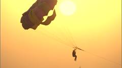 People parasailing at sunset. Stock Footage