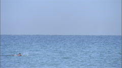 A man swims across the ocean. - stock footage