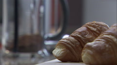 Coffee poured into a glass with two breakfast croissants. Stock Footage