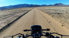 Viewpoint Motorcycle Speeding Down Dirt Road In Desert- Fast Motion Stock Footage