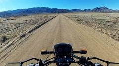 Viewpoint Motorcycle Speeding Down Dirt Road In Desert - stock footage