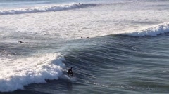 Surfers Surfing on Rough Sea Stock Footage