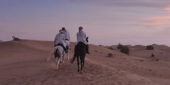 Men riding horses in a desert. - stock footage