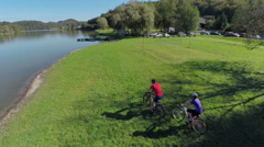 Cyclist drive on the grass near the lake Stock Footage