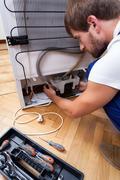 Handyman repairs the fridge Stock Photos