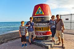 Family posing at Southernmost Point marker, Key West, Florida, USA Stock Photos