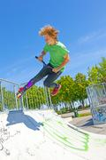 Boy jumps with his scooter at the skate park Stock Photos