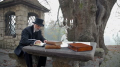 Writing a poem at a stone table in front of big tree Stock Footage