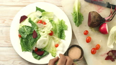 Healthy conscious hand chef tossing a tasty organic green salad, Top view Stock Footage