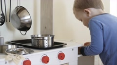Adorable boy playing with his toy kitchen Stock Footage