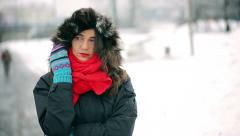 Sad woman standing alone in the park at winter time Stock Footage