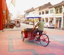 Penang A pedicab driver pedals his cycle rickshaw, laden with cargo, across the  - stock photo