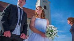 In front of the church the bride throws a bouquet  - stock footage