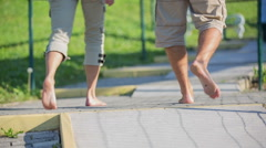 Couple walk barefoot on the footpath in the park Stock Footage
