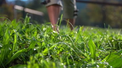 While walking on the grass drops of water atomising around Stock Footage