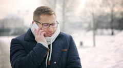 Happy man talking on cellphone in the park at winter time and tremble Stock Footage
