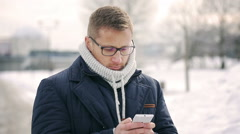Man typing message on cellphone in the snowy park and smiling to the camera - stock footage