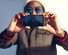 Technology and people concept - modern stylish african man makes selfie, scre - stock photo