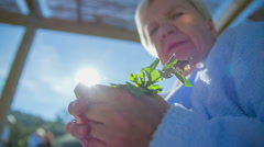 Older woman looking the flower in her hand Stock Footage