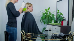 Hair dresser refers the hair colour on the woman  - stock footage