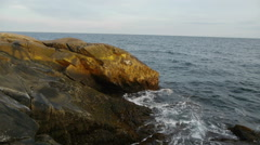 Pan across coast with sun on rocks - stock footage