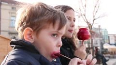 Adorable Little Boy And A Girl Eating Lollipop And Candied Apple In The Park Stock Footage