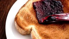 Spreading blueberry blackberry blackcurrant jam on crunchy toast in slow motion - stock footage