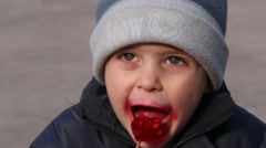 Cute Little Boy Eating Red Lollipop In Adorable Way Close Up View  Outdoors Stock Footage