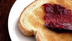 Strawberry raspberry jam being spread on toast in slow motion Stock Footage