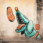 Penang  Large mural of a blue, cartoon style dog catching a steak in the air Stock Photos