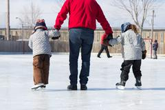 Family having fun at the skating rink - stock photo
