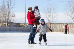 Happy family at the skating rink - stock photo