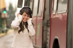 woman walking on the city street covering her ears concept of noise pollution - stock photo