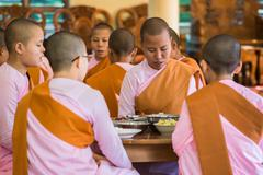 Buddhist nuns pray in their nunnery before the meal - stock photo