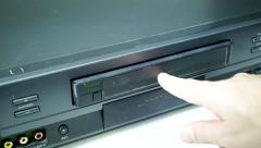 VHS tape being inserted into a VHS machine Stock Footage