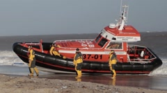 Caister lifeboat being towed onto beach Stock Footage