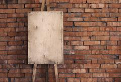 Blank grunge easel on a brick wall, art background Stock Photos