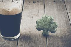 Pint of Stout Beer with Green Shamrock with Vintage Film Filter Stock Photos