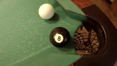 Player successfully hits 8 ball in corner pocket on a green pool table Stock Footage