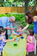 Family Dyes Easter Eggs Outside - stock photo