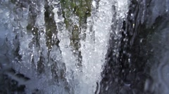 Waterfall runs down the icicles super slow motion Stock Footage