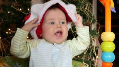 Baby tugs at santa hat Stock Footage