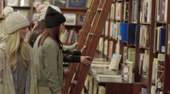 Multi-ethnic Teens Search For Books In A Library Or Bookstore Stock Footage