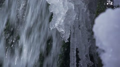 Water drops fall from an icicle in background waterfall in slow motion Stock Footage
