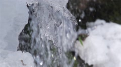 Water drops fall from an icicle in background waterfall super slow motion Stock Footage