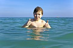 boy with red hair is enjoying the clear warm water at the beautiful beach - stock photo