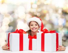 smiling girl in santa helper hat with gift boxes - stock photo