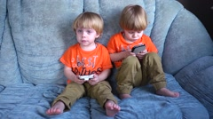 Kids twins having fun playing with mobile cell phones on a couch Stock Footage